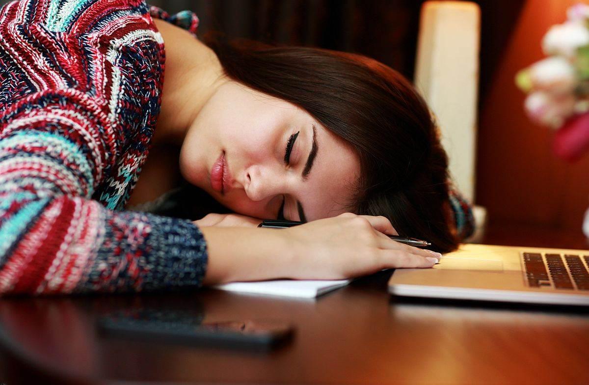umorna zena spava za stolom