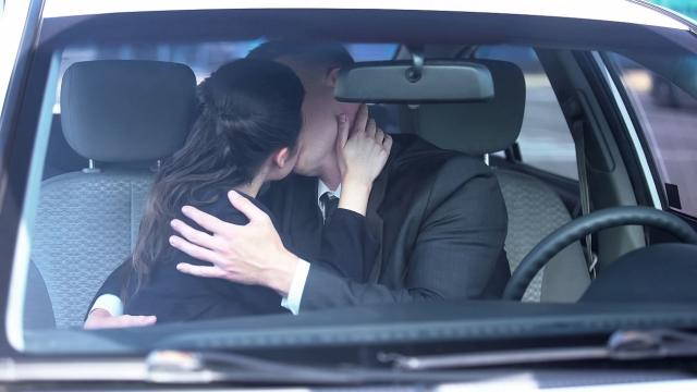 muskarac i zena se ljube na parkingu